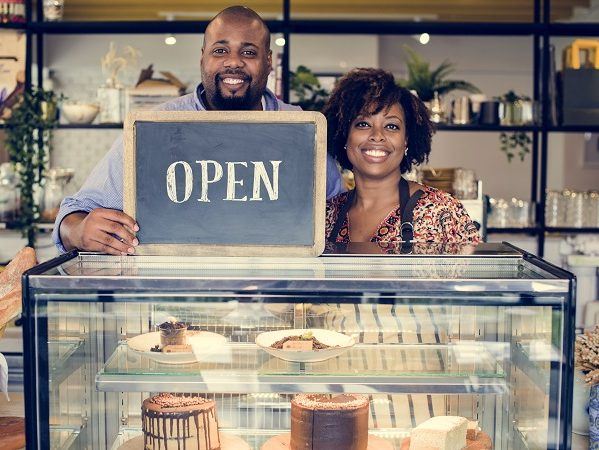 Cake cafe owners with open sign